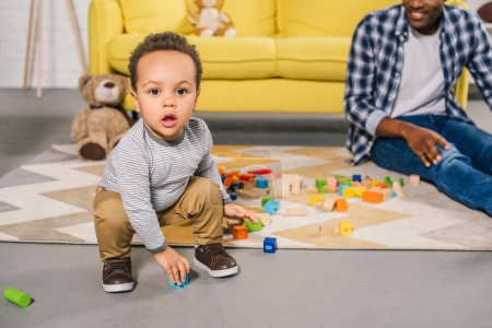 adorable african american toddler looking at camera while playing with father at home