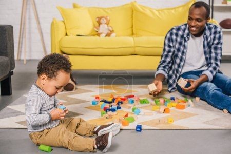 smiling young father looking at adorable child playing with colorful blocks at home
