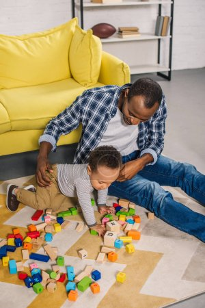 high angle view of young father with cute little son playing with colorful blocks at home