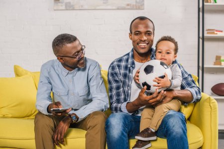 happy senior man holding remote controller and looking at smiling young father and son sitting on sofa with soccer ball
