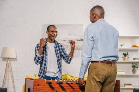 senior father and smiling adult son playing table football at home
