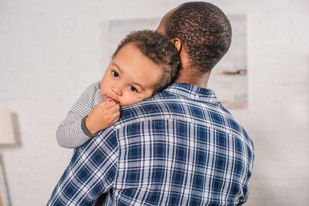 Photo pour Jeune père afro-américain portant adorable petit fils à la maison - image libre de droit
