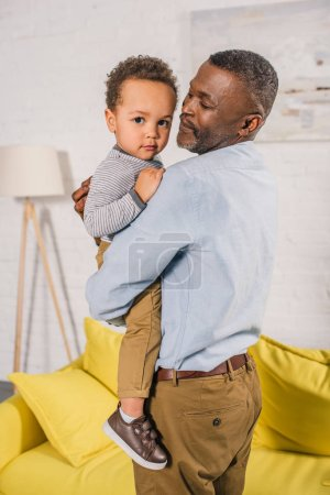 happy african american grandfather carrying adorable little grandchild at home