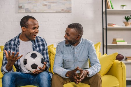 happy father and adult son with soccer ball smiling each other while sitting on sofa