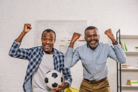 cheerful father and adult son with soccer ball triumphing and smiling at camera