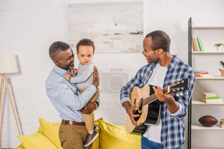 smiling young man playing guitar and looking at happy grandfather holding grandson at home