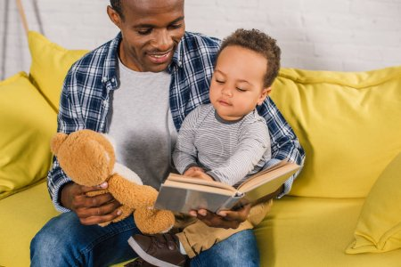 cropped shot of smiling father holding teddy bear and reading book to little son