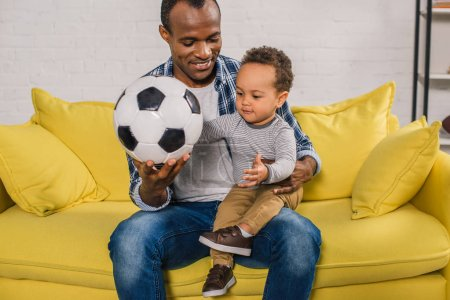 happy young father holding soccer ball while sitting with adorable little son on sofa