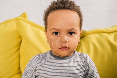 close-up portrait of adorable african american toddler looking at camera while sitting on yellow couch