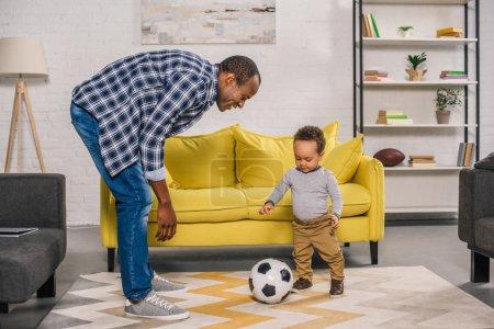happy young father looking at smiling little son playing with soccer ball at home