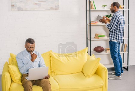 senior man using laptop while adult son holding book near bookshelves at home