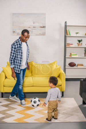 happy african american father and little son playing with soccer ball at home