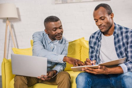 senior man using laptop and looking at adult son taking notes in notepad at home