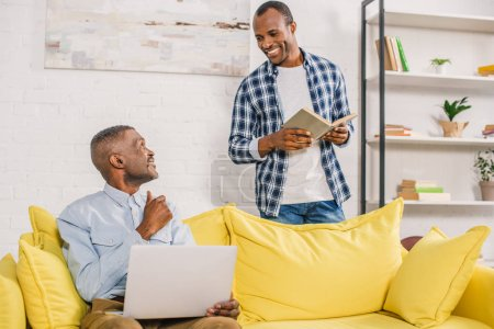 senior man with laptop and adult son with book smiling each other at home