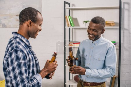 smiling african american father with adult son holding beer bottles at home
