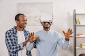 smiling young man looking at happy senior father using virtual reality headset at home