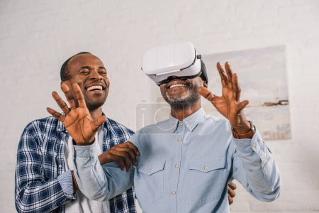 smiling young man looking at happy senior father using virtual reality headset