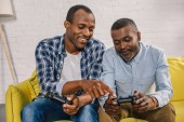 happy african american father and adult son using joysticks together at home