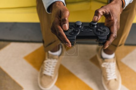 Photo for Cropped shot of african american man sitting on sofa and playing with joystick - Royalty Free Image