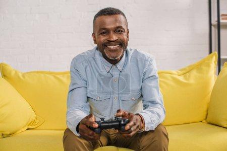happy senior man using joystick and smiling at camera