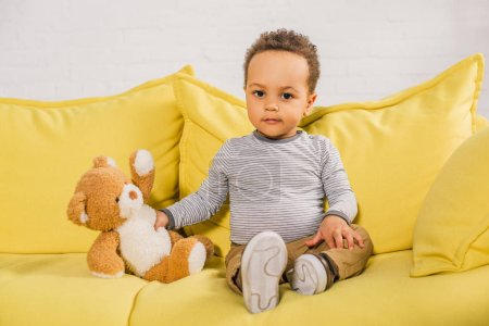 adorable african american kid holding teddy bear and looking at camera while sitting on yellow couch