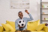 cheerful african american man holding soccer ball and looking at camera while sitting on sofa at home