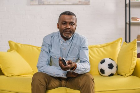 african american man using remote controller and looking at camera while sitting on sofa with soccer ball
