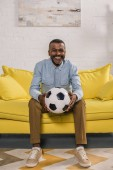 smiling african american man sitting on sofa and holding soccer ball