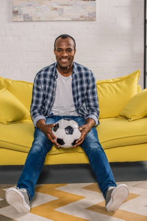 cheerful african american man holding soccer ball and smiling at camera while sitting on couch