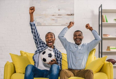 cheerful african american father with adult son holding soccer ball and smiling at camera at home