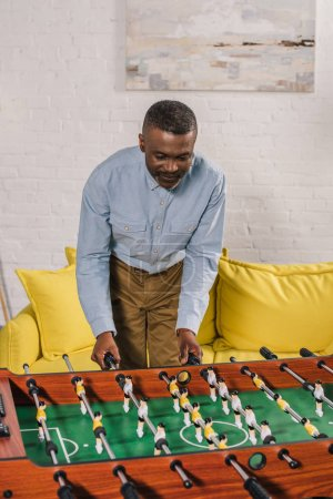 smiling african american man playing table football at home