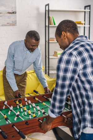 happy senior father and adult son playing table football at home