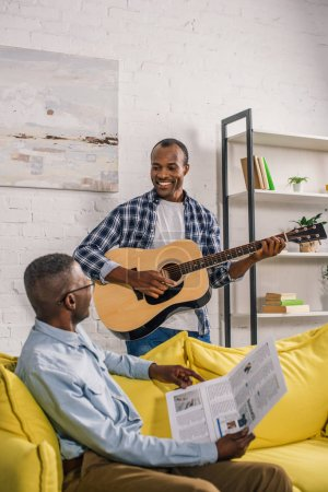 happy senior man with newspaper and adult son with guitar smiling each other at home