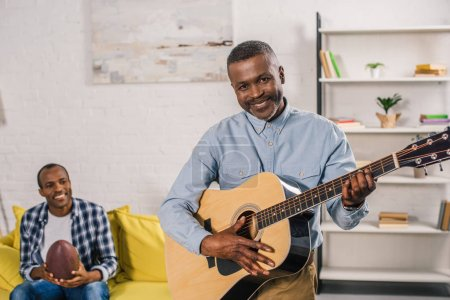 senior man playing acoustic guitar and smiling at camera while adult son holding rugby ball behind