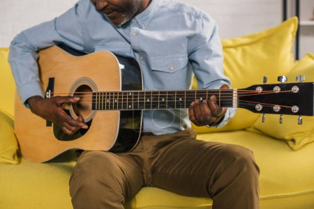 cropped shot of senior african american man playing acoustic guitar at home