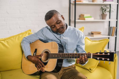smiling african american man playing acoustic guitar at home