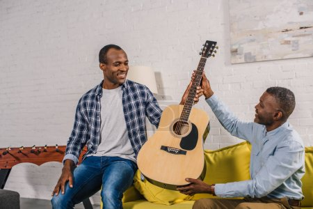 happy senior man giving guitar to smiling adult son at home