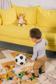 high angle view of adorable little african american child playing with soccer ball and colorful blocks at home