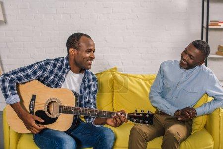smiling senior man looking at adult son playing guitar at home