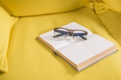 close-up view of eyeglasses and book with blank pages on yellow couch