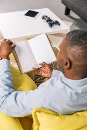 high angle view of senior african american man reading book while sitting at home