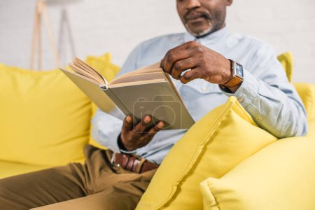 cropped shot of senior african american man reading book while sitting at home