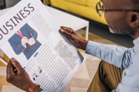 cropped shot of senior african american man in eyeglasses reading business newspaper