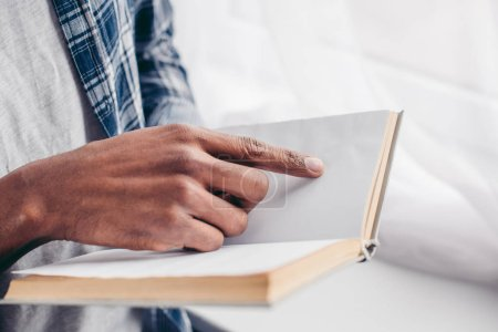 cropped shot of african american man reading book with blank pages