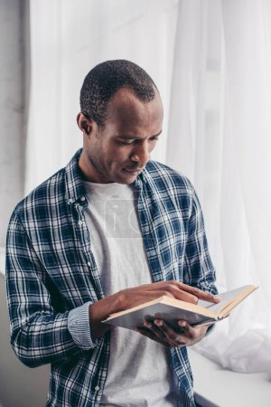 focused young african american man standing and reading book