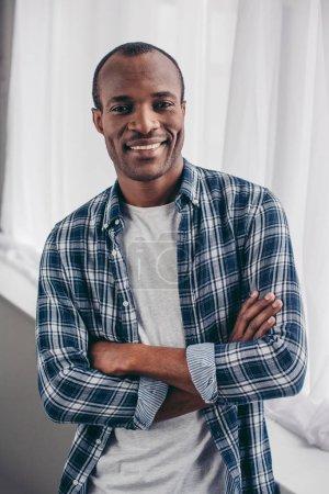 Photo pour Beau jeune homme afro-américain debout avec les bras croisés et souriant à la caméra - image libre de droit