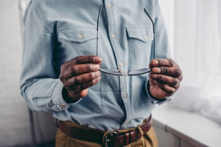 cropped shot of senior african american man holding eyeglasses