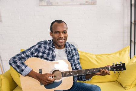 handsome african american man playing acoustic guitar and smiling at camera