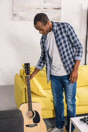 Photo for Young african american man holding acoustic guitar at home - Royalty Free Image