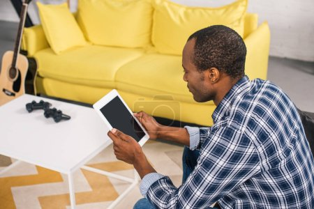 high angle view of african american man using digital tablet with blank screen at home